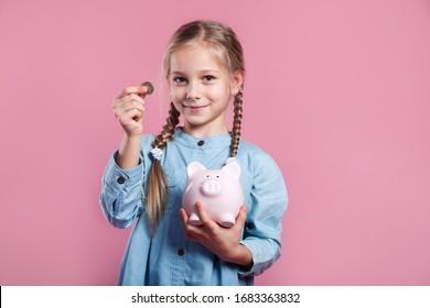 Little girl saving money in a piggybank on pink background