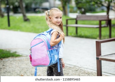Little girl with a school backpack. The concept of school, study, education, friendship, childhood.