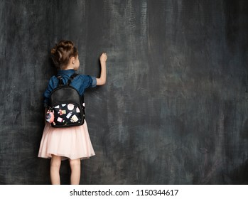 Little girl with school bag near blackboard in classroom.Pupil is writing on a chalkboard in a denim shirt and a pink skirt. Education and elementary school concept.