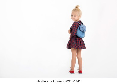 the little girl in school clothes and a backpack has turned the head behind the back and has looked back