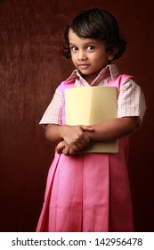 Little girl in school uniform holds a book in hand