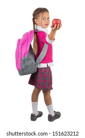 Little girl in school uniform and pink backpack gives you a red apple, isolated