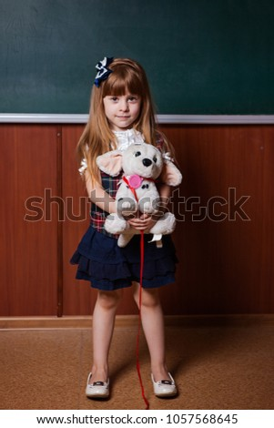513dd2e008e5 little girl in school uniform posing against chalkboard background with  soft toy dog