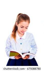 Little girl in school uniform reading a book and smiling, isolated on white background. The modern concept of school, education and development.
