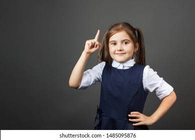 Little girl in a school uniform show a sigh. Attention! Oh, an idea! Do not miss! Copy space. The concept of education, back to school, etc.