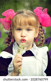 little girl in school uniform sitting on the grass and blowing dandelion