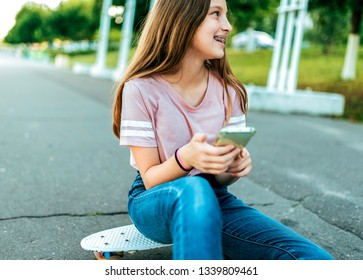 A little girl schoolgirl of 13-15 years old, on street she sits on a skateboard in summer in park. In hands of phone, online application, Internet social networks, smiling rejoices and laughs happy.