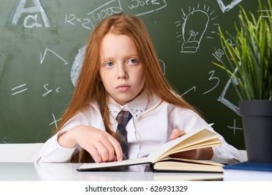 Little girl schoolgirl with book sitting at table