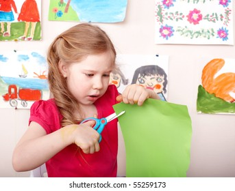 Little girl  with scissors cut paper at home.