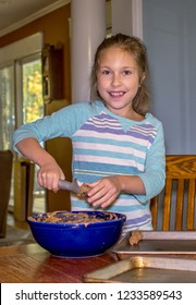 little girl scoops dough onto cookie sheets, for chocolate chip cookies