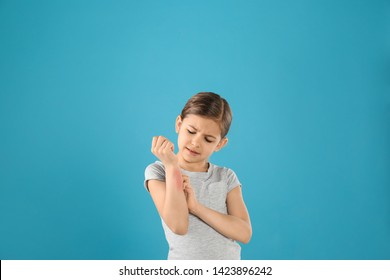 Little girl scratching forearm on color background. Allergy symptoms