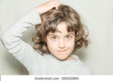 little girl scratching her head