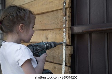 Little girl with screwdriver in hands tightening bolts on wooden background,closeup