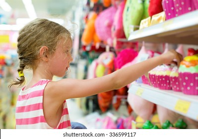 Little girl selecting toy on shelves in supermarket.