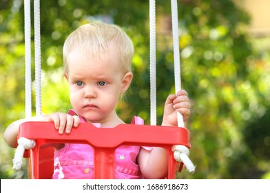 Little girl is serious, sad and pensive. Swing summer. Sunny hot day. Bokeh, close up.