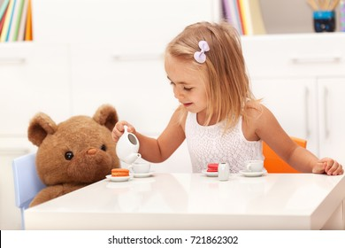 Little girl serving her toy bear - pouring tea and eating colorful sweet cookies