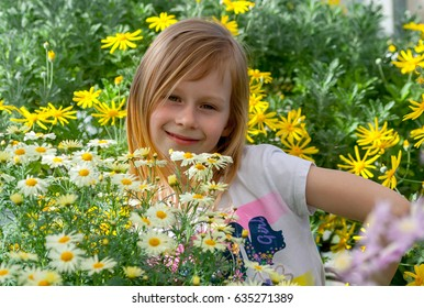 little girl seven years old, surrounded by daisy flowers in a botanical garden, eyes open, looking at camera, cheerful and smiling, long blond, wheat hair, happy baby, sunny, bright day, arm at waist