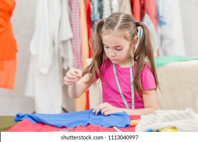 little girl sewing with a needle and thread. Hobby sewing concept