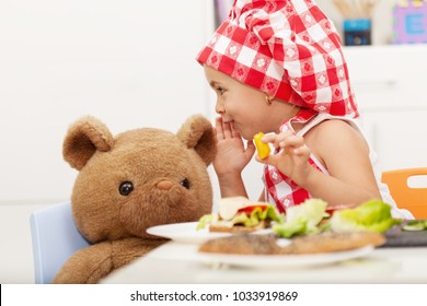 Little girl sharing secrets with her teddy bear - having a snack at the table