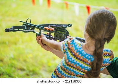 Little girl shooting crossbow at summer outdoor shooting range.
