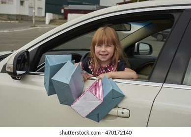 little girl with shopping from the car looks