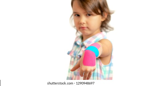 little girl showing her bandaged wrist with kinesio tapes