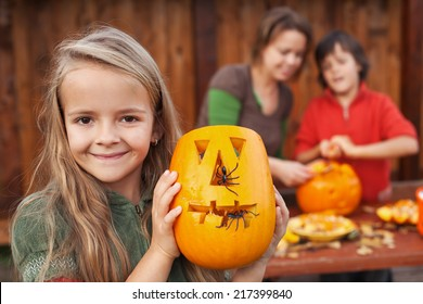 Little girl showing her freshly carved Halloween jack-o-lantern