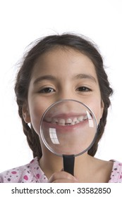 Little girl showing her teeth through a magnifying glass