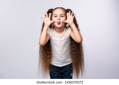 Little girl showing her tongue. Child teasing and playing on white background. Happy child