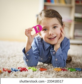 Little girl showing letter D learning the letters at home