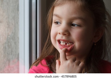 Little girl showing a lost tooth look out the window