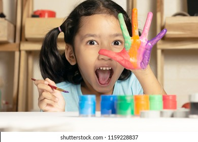 The little girl is showing painted color on hand with happiness. Select focus shallow depth of field.