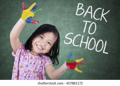 Little girl showing painted hands with back to school text on chalkboard