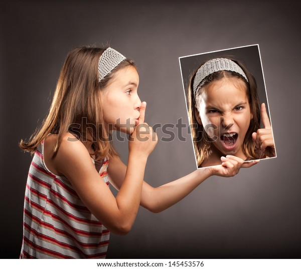 little girl showing silence gesture and holding a portrait of herself