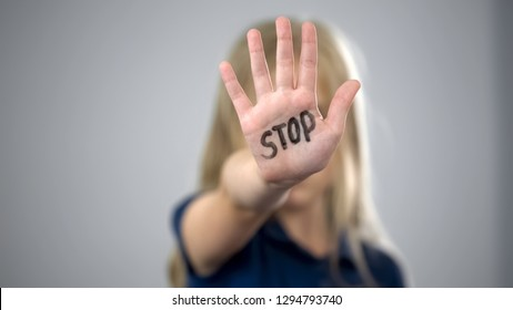 Little girl showing stop sign, child abuse issue, cruelty in family, awareness