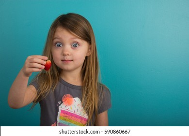 Little girl showing a strawberry