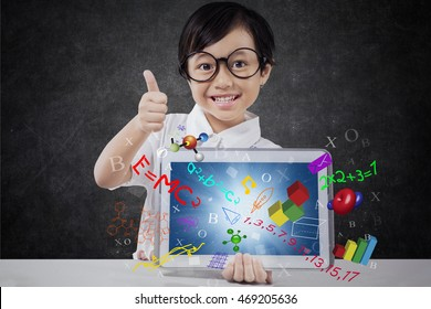 Little girl showing thumb up while holding a digital tablet with formula of science, math, and physics on the screen