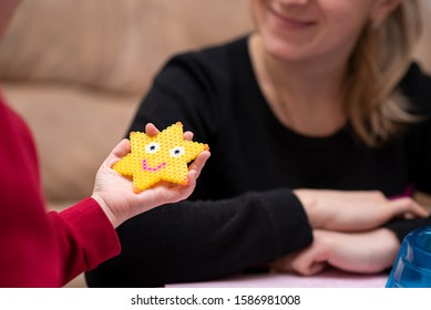 Little girl shows mom just crafted art toy from perler beads, beautiful smiled star. Fusible colorful beads. Toy that develops the imagination and creativity of child.