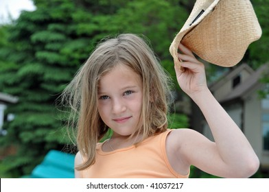 a little girl shows off and raises her cowboy hat