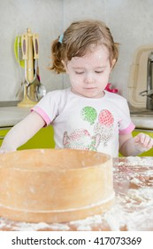 Little girl sifts the flour for the dough