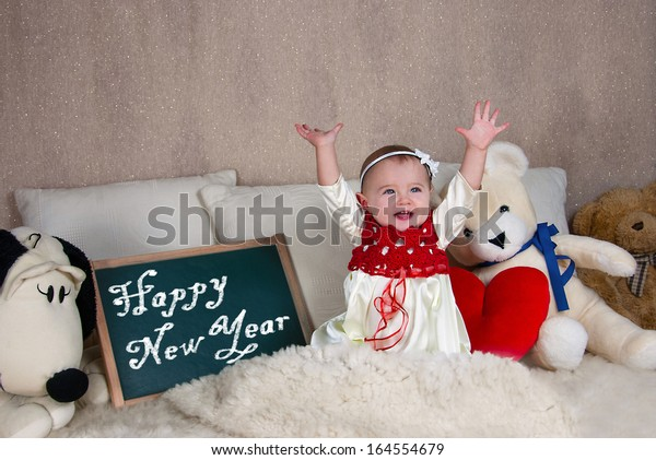 Little girl with a sign with the words Happy New Year.
