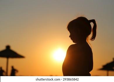 little girl silhouette at sunset beach