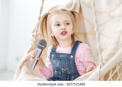 A little girl is singing karaoke into the microphone. The concept of childhood, performer, life style, music.