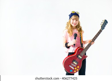little girl singing a song with a microphone and a guitar on a white background. Isolate