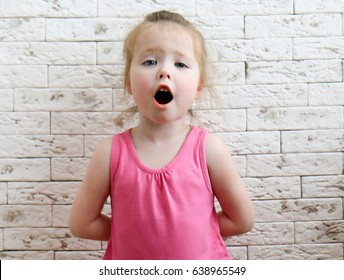 Little girl sings in the background of a brick wall. The child opens his mouth and tries to sing. A child's voice.
