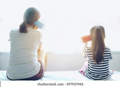 Little girl and sister having a phone call with tin cans and both are siting on the bed .back view.Family concept