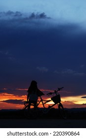 little girl sit on bicycle watching the  beautiful sunset.Silhouette,