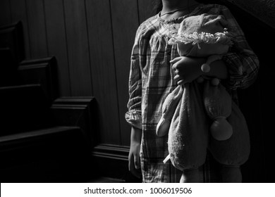 A little girl sits alone with a rabbit doll on the stairs.