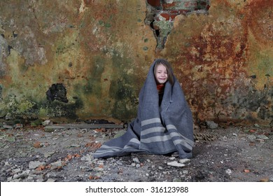 Little girl sits in basement wrapped in blanket and crying with tears on face - loneliness, poverty, despair concept