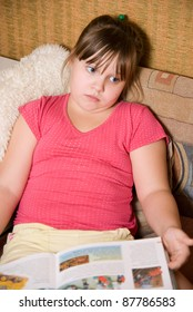 The little girl sits with the book on a sofa
